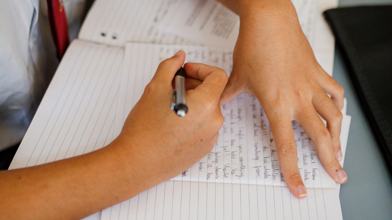Photo of hands writing in an exercise book